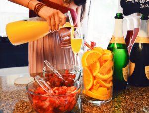 femme se servant un mimosa pendant un brunch