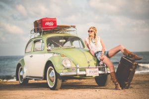 Jeune femme look vintage appuyée contre sapetite voiture verte avec valises sur le toit