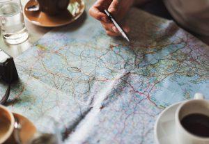 Main avec stylo en train de noter des lieux sur une carte