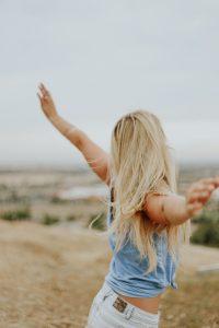 Jeune femme blonde de dos les bras écartés face au vent