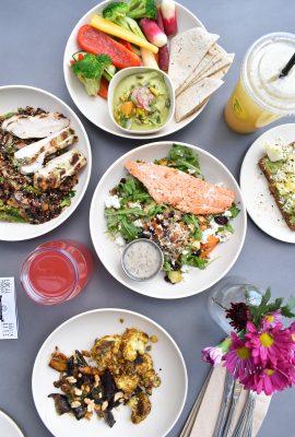 vue de haut de plats sur une table grise assiettes blanches avec poisson viande légumes