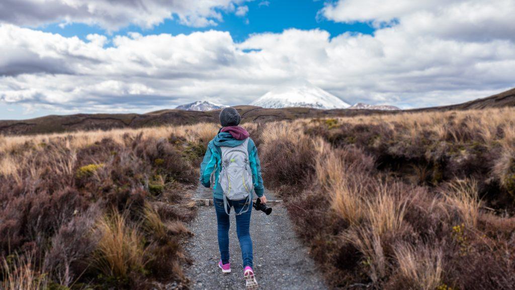 Jeune femme en train de marcher sur un sentier de randonnée en montagne