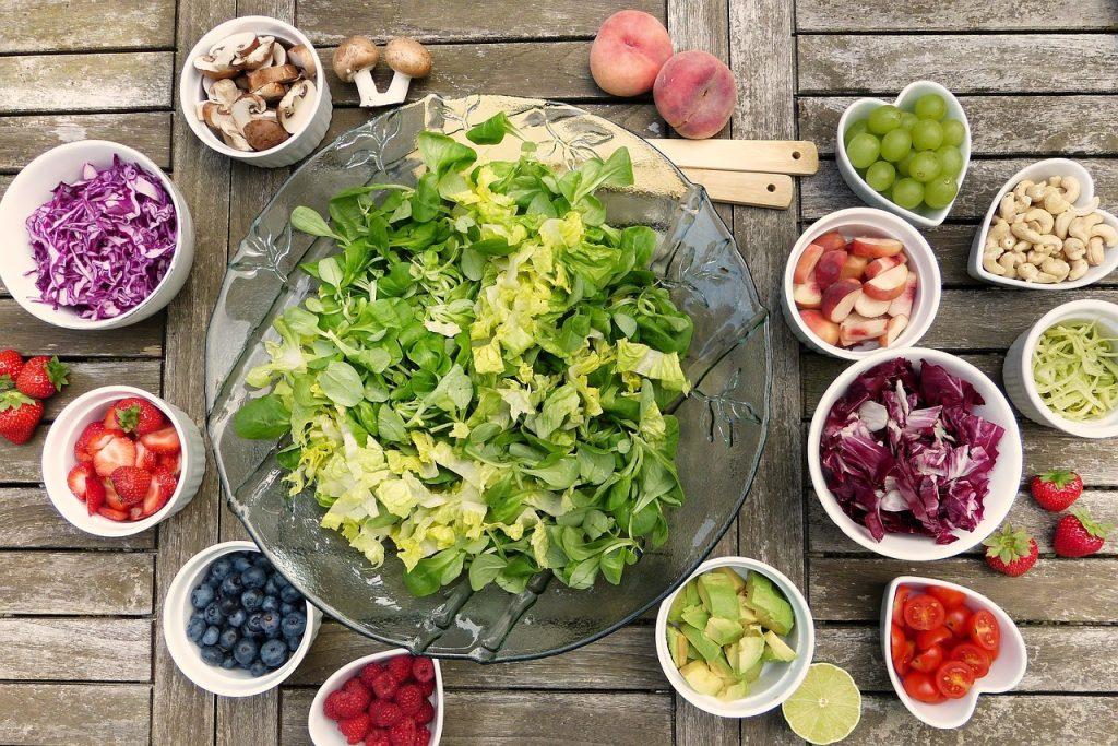 saladier avec salade entouré de petits bols avec ingrédients pour salade composée