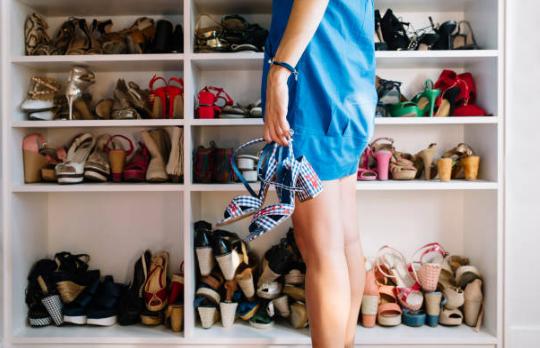 femme tenant une paire de chaussures à la main debout devant un placard plein de chaussures