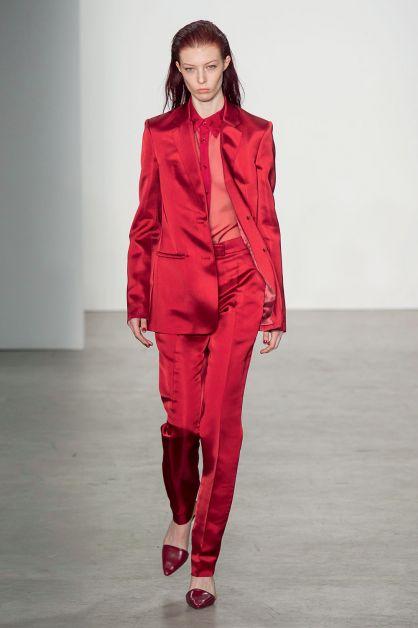 top model défilé femme portant un costume rouge satiné