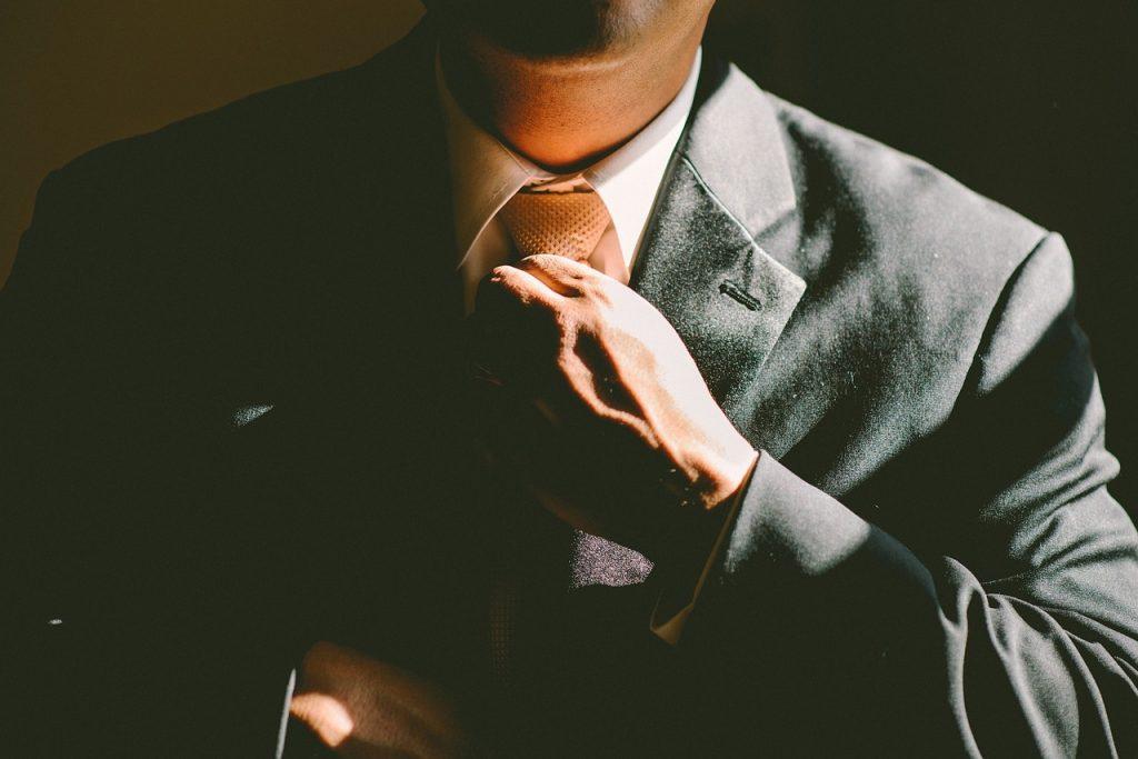 zoom sur le buste d'un homme qui ajuste sa cravate et porte un costume foncé et une chemise blanche
