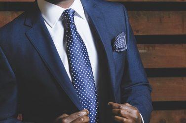 zoom sur le buste d'un homme portant un costume bleu marine une chemise blanche et une cravate bleu marine