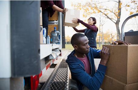 personnes chargeant des cartons de déménagement dans un camion et écrivant sur un carton