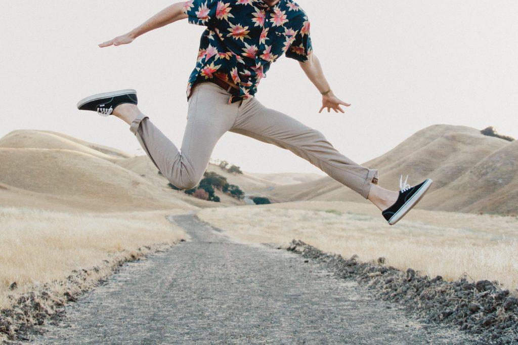 homme sautant dans les airs portant un chino clair et une chemise à motifs floraux