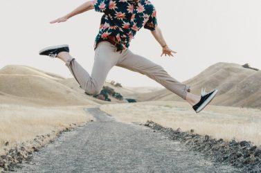 homme faisant un saut dans les airs portant un chino clair et une chemise à motifs floraux