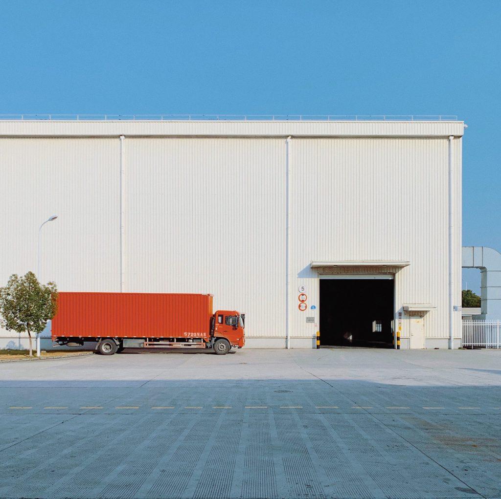 Un camion rouge devant un entrepôt