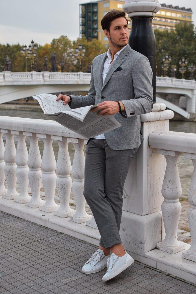 homme lisant un journal debout sur un pont portant un chino gris une veste blazer grise et des baskets blanches