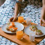 Plateau pour le petit-déjeuner posé sur la couette d'un lit
