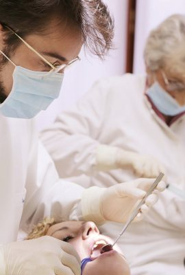 Dentiste qui examine les dents d'une patiente