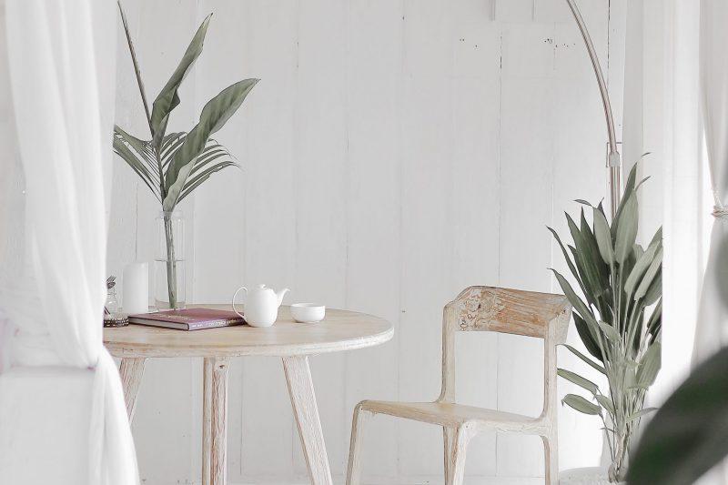 coin d'une maison décoré en blanc avec un table une chaise un lampe et des plantes