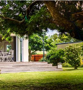 extérieur de maison avec terrasse et balançoire en pneu accrochée à un arbre