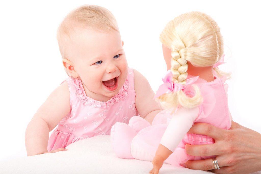 bébé qui sourit devant sa poupée